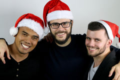 Three friends smiling for Christmas. On a gray background Royalty Free Stock Images