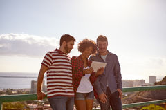 Three friends smiling at a tablet Stock Images