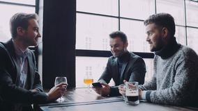 Three friends spending time together in the pub, the man in the suit shows smth on his phone, everybody is pleased with. The result and they toast. Real stock video footage