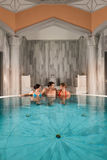 Three friends in swimming pool or thermal bath Stock Photo
