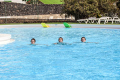 Three friends swimming in a row Stock Photo