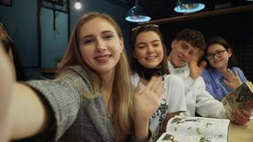 Three friends take a selfie and wave at the camera with a greetings sitting in a coffee house with books and notes. Friends take a selfie and wave at the camera stock video