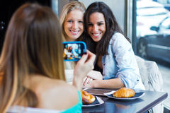 Three friends taking photos with a smartphone Royalty Free Stock Images