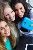 Three friends taking photos with a smartphone Stock Images