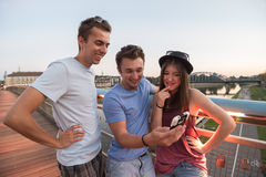 Three Friends Taking Selfie On The Bridge. A group of young adult friends smiling and taking selfie royalty free stock image