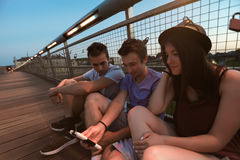 Three Friends Taking Selfie On The Bridge. A group of young adult friends smiling and taking selfie stock photo