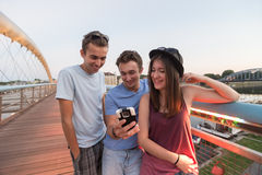 Three Friends Taking Selfie On The Bridge. A group of young adult friends smiling and taking selfie royalty free stock photos