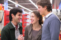 Three friends talk in shop Royalty Free Stock Images