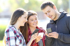 Three friends talking holding their smart phones. Three friends talking together and holding everyone their smart phones standing in the street Royalty Free Stock Image