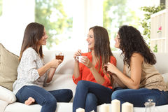 Three friends talking at home. Three happy friends talking and drinking coffee and tea sitting on a couch at home Stock Image