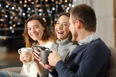 Three friends talking and laughing in the night at home. Three friends talking and laughing in the night sitting on a couch in the living room at home stock photos