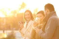 Three friends talking outdoors at sunset. Three funny friends talking outdoors and drinking coffee at sunset Stock Photos