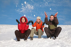 Three friends throw snows. Three friends sit on snow and throw snows stock images