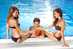 Three friends toasting each other at the pool Royalty Free Stock Photo