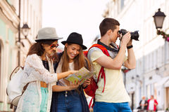 Three friends together with city map and camera Stock Photography