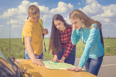 Three friends travel. Three friends wanderer searching direction on location map on old car, two girls and guy tourist searching road to hotel or direction seaon royalty free stock photography