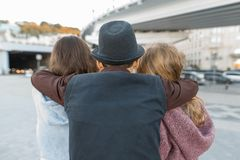 Three friends, view from the back of young teenager boy hugging two girls by the shoulders. Children look ahead, city life stock photography