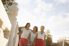 Three Friends Walking Across a Bridge royalty free stock photo