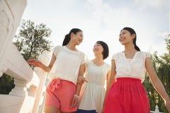 Three Friends Walking Across a Bridge royalty free stock photos