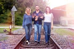 Three friends walking on train tracks Stock Photo