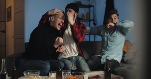 Three friends watching football match on tv at home, cheering best soccer team. Emotion. Mens fans celebrate winning. stock video footage