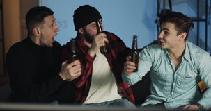 Three friends watching football match on tv at home, cheering best soccer team. Emotion. Mens fans celebrate winning. stock footage