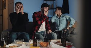 Three friends watching football match on tv at home, disappointed they team. Three friends watching football match on tv at home, disappointed they team stock footage