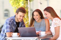 Three friends watching media content on laptop in a bar. Three happy friends watching on-line media content on laptop in a bar stock photo