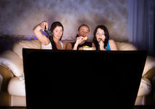 Three friends are watching TV Royalty Free Stock Image