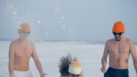 Three friends wearing swimming closes play with the snow. Two men and a woman in swimwear  play with the fresh snow stock footage