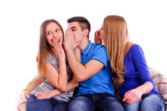 Three friends whispering secrets to shocked brunet Royalty Free Stock Photos