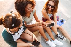 Three friends woman using mobile phones listening music with earphones. Royalty Free Stock Image