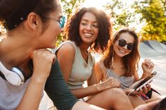 Three friends woman using mobile phones listening music with earphones. Stock Images