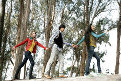 Three friends in woods. A view of three friends enjoying being together and having fun, walking hand-in-hand in the woods Stock Photo