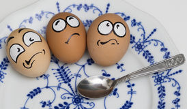 Three frightened egg face on blue plate Royalty Free Stock Photo