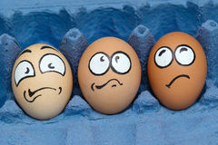 Three frightened egg face  waiting cooking. Three frightened egg face in blue paper eggshell Stock Image