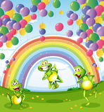 Three frogs under the floating balloons near the rainbow Stock Photos