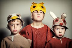 Three frown boys in masks of sparrow, owl and rabbit Royalty Free Stock Photography