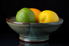Three fruit in a bowl. An orange, lemon, and lime rest in a pottery bowl.  The bowl seems to float on a black background Stock Image