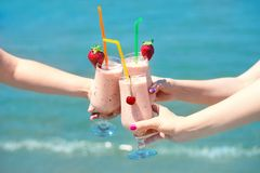 Three fruit juice smoothie in classic glass cups of berry fruits turquois sea water background. Three girls cheers. Three fruit juice smoothie in classic glass royalty free stock photography