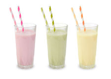 Three fruit smoothies. In glasses with colorful straws Stock Images