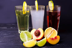 Three fruits soft-drinks with lemon on a edge of a glass. Lime, lemon and peach on a bottom on a dark background. Royalty Free Stock Image