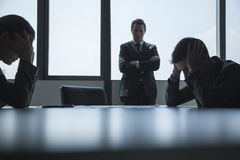 Three frustrated and overworked business people in the board room with arms crossed and head in hands. Stock Photo