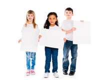 Three funny children holding paper blanks in hands Royalty Free Stock Image