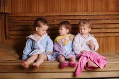 Three funny children in sauna Stock Photos