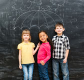 Three funny children with umbrella drawn on the blackboard Royalty Free Stock Photography