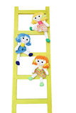 Three funny doll on a wooden ladder Royalty Free Stock Photos
