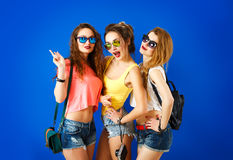 Three Funny Hipster Girls on Blue Background. Three Funny Street Style Hipster Girls Posing at Blue Background. Trendy Casual Fashion Outfit in Summer. Youth Stock Image