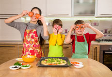 Three funny kids making the pizza Stock Photos