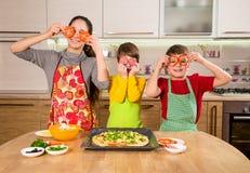 Three funny kids making the pizza. Three funny kids with food on eyes making the pizza, in the kitchen interior stock photos